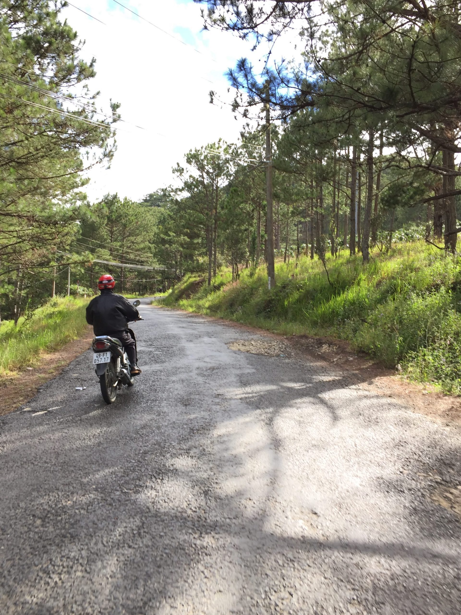 A man riding a motorbike in the pass of Dalat city