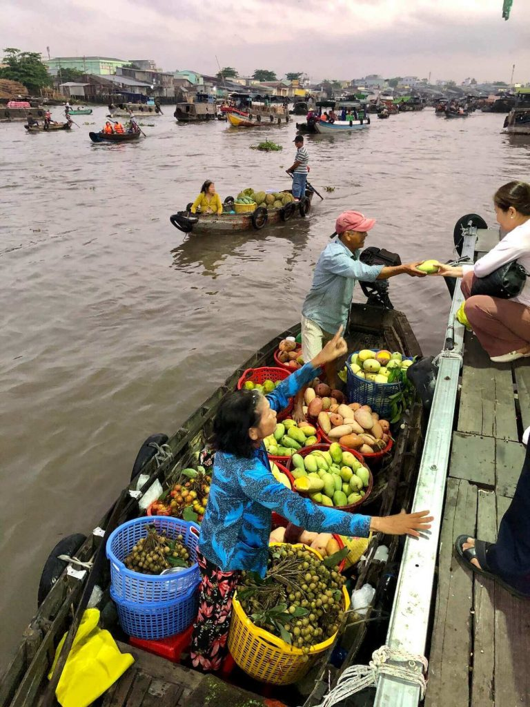People buy and sell fruits on a floating market at Can Tho during the coronavirus season
