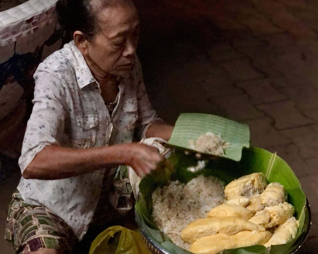 A woman sells durian sticky rice