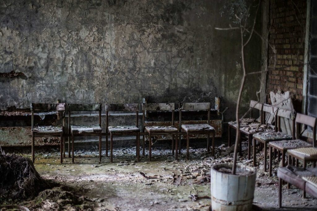 An abandoned room with rusted chairs and dead tree in Pripyat, Ukraine