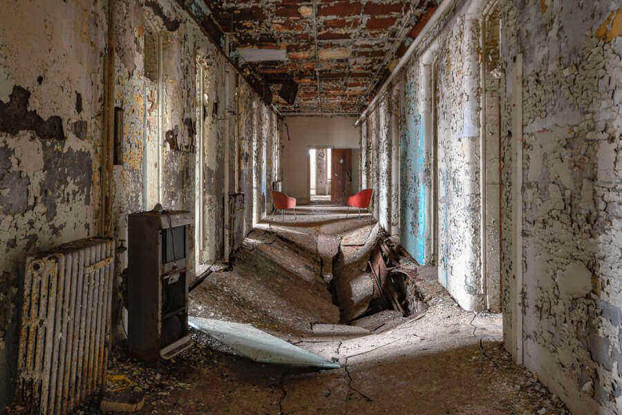 runied hall way in willard asylum, a creepy abandoned hospital