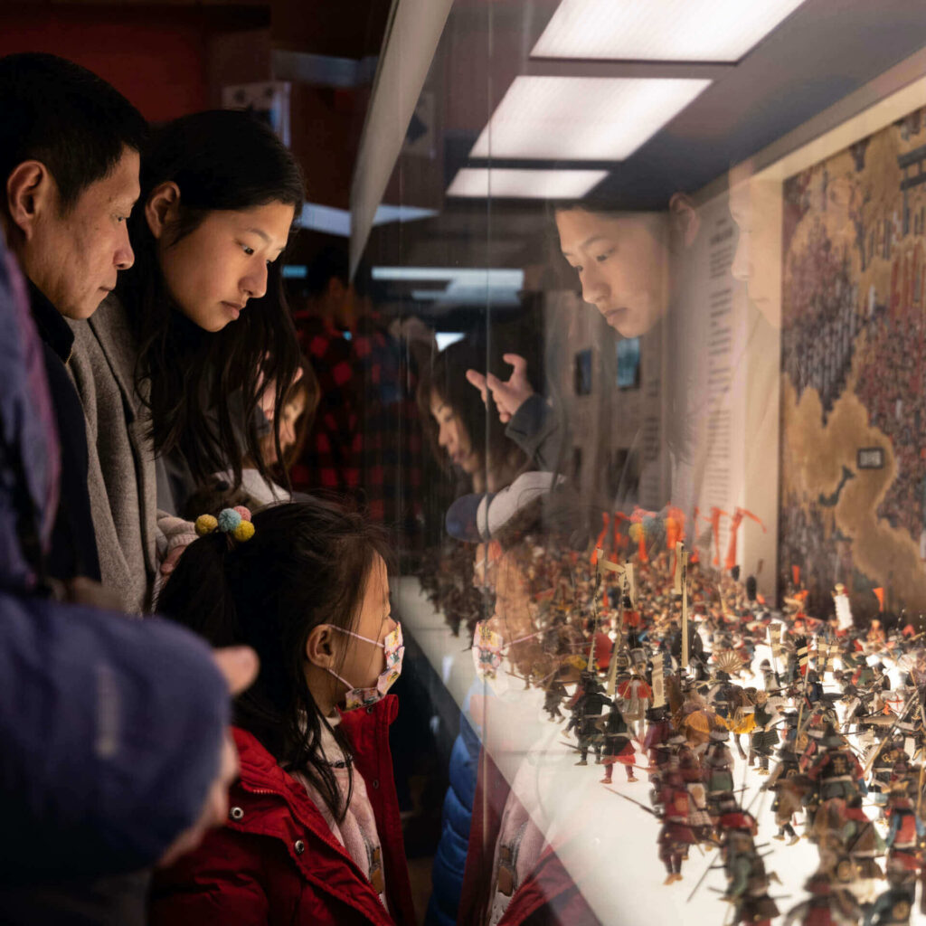 asian parents take their daughter to a museum for summer vacation