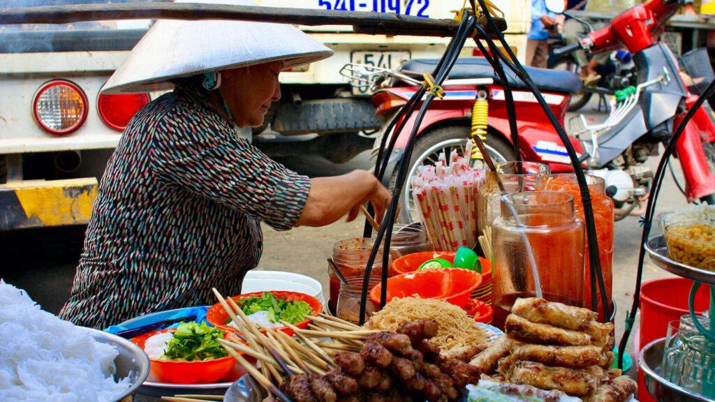 a woman selling bun thit nuong on the street of saigon