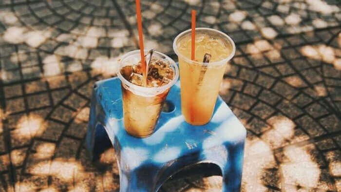 a cup of coffee and a cup of ice tea put on a low chair